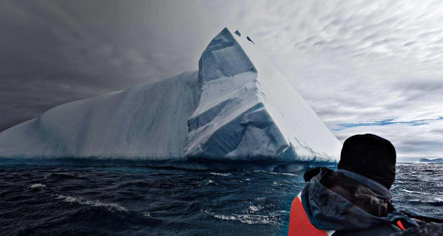 IDU Mortality Metaphor: A man views a large iceberg formation at close range - Avoid the risk of deceased fraud through comprehensive mortality screening solutions