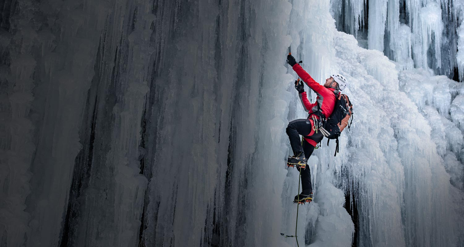 A climber expertly scaling a treacherous wall of ice in full climbing gear
